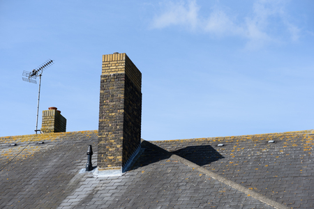 Single brick chimney on a grey tiled roof with blue sky background