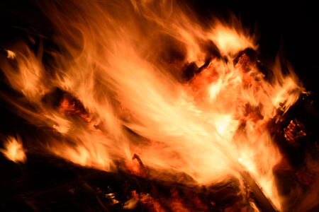 Burning raging fire at night with intentional movement of the flames creating a dynamic light effect and intentional blurred motion