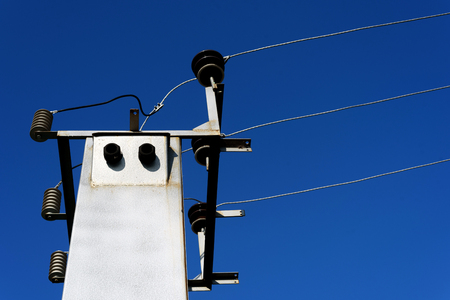 Image of an electrical substation and power lines set against a blue sky outdoors during the day