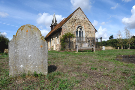 Single unmarked and worn gravestone in a churchyard with an old ancient church in the background with nobody