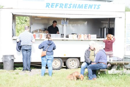CHELMSFORD, ESSEX/ENGLAND - 1ST JUNE 2019 - People visiting a car boot sale in Boreham Essex buying fast food bugers and where they can also buy cheap and unusual items during the summer of 2019