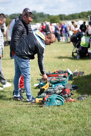 CHELMSFORD, ESSEX/ENGLAND - 1ST JUNE 2019 - Men visiting a car boot sale in Boreham Essex where they are looking at drills and tools for work and can also buy cheap and unusual items during the summer of 2019