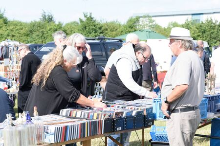CHELMSFORD, ESSEX/ENGLAND - 1ST JUNE 2019 - People visiting a car boot sale in Boreham Essex browsing CDs and where they can also buy cheap and unusual items during the summer of 2019