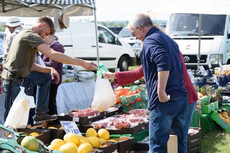 CHELMSFORD, ESSEX/ENGLAND - 1ST JUNE 2019 - People visiting a car boot sale in Boreham Essex buying fruit and vegetables and where they can also buy cheap and unusual items during the summer of 2019