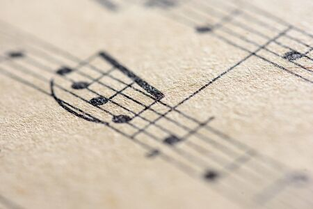 Aged sepia effect of a macro closeup shot of musical notes written on paper notes in traditional sheet music format
