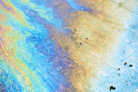 Toxic colours of oil and water in a chemical spill creating a psychedelic blur of rainbow colours. Copyspace area for environmental and pollution based themes and designs. Stock Photo