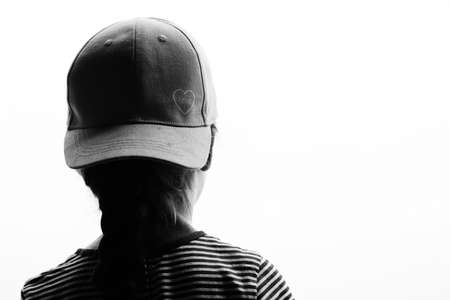 Young girl wearing a baseball hat with love symbol front to back in silhouette in black and white with white copyspace area
