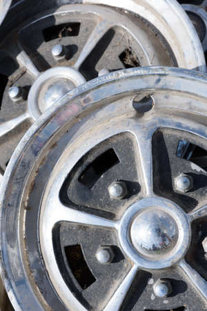 Closeup of tow car wheel trims in alloy metal silver with dirt and grime showing their used condition