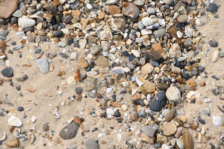 Pebbles and sand merge together on the sides of a sea coastal water area
