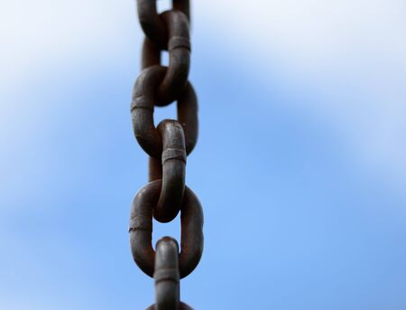 Metal chain in a closeup view with blue sky and clouds with copyspace area for freedom slavery persecution based design s and ideas