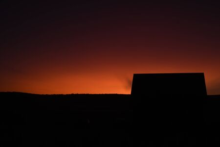Bright orange cloudless sky with a black silhouette of a wooden building with copyspace area for late evening or romantic based designs and ideas Stock fotó