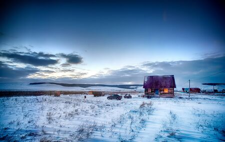 Single isolated house with snow and hills in the background set during the winter time season 版權商用圖片