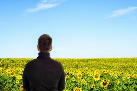 Man wearing a black top with back to camera facing out towards a sunflower field with copyspace area for farming and floral based ideas and designs