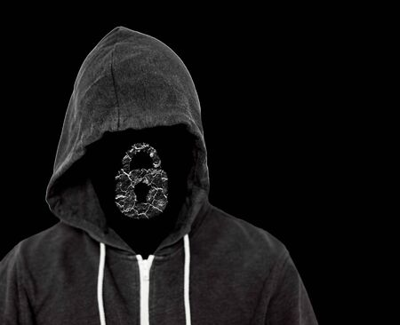 Hooded menacing man with unseen face wearing a black top with a computer lock which has been broken by the hackers criminal work Zdjęcie Seryjne