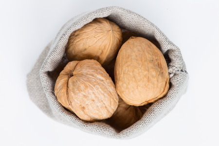 linen bag: Walnuts in the linen bag on a white background Stock Photo