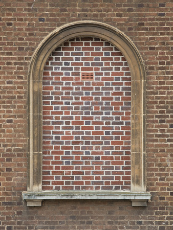 A Bricked In Arched Window with a breeze brick added for ventilation  Stock Photo