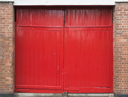 loading bay: A bright red loading bay door, originally stable style panels have been added to close of the top section  Stock Photo