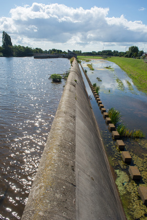 A spillway wall seperates a river from a flood channel. Фото со стока - 32098727