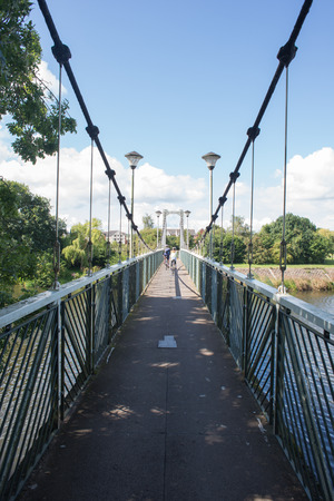 focal point: A suspension bridge with cyclists in the distant focal point. Stock Photo