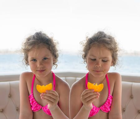 Children with oranges. Happy little girls eat oranges near the sea. Photo collage.