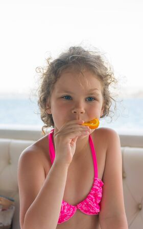 Baby with orange. Happy little girl eating orange near the sea.