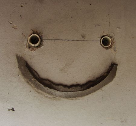 odd repair in a wall looking like a smiley photo
