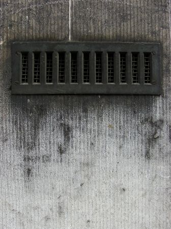 metal ventilation vent in a worn dirty gray wall photo