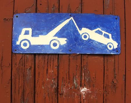 hand painted tow sign on a red brown wooden garage door