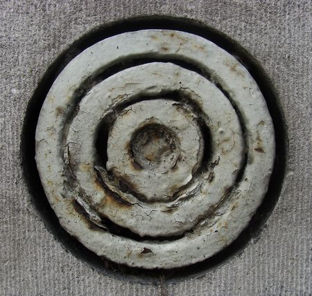 circular round rusty ventilation shaft in a gray stone wall                                photo