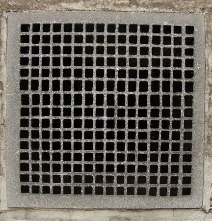 irregular metal grid from a ventilation shaft in a concrete wall                            photo