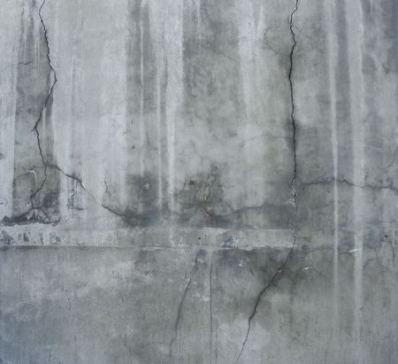 large section of a dirty grunge gray wall with white leaks and cracks
