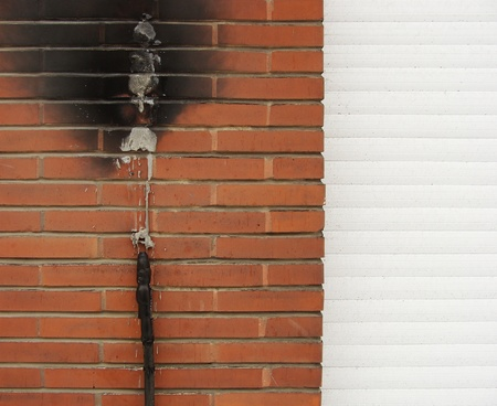 ELECTRICAL OUTLET: short circuit fire damage on a brick wall