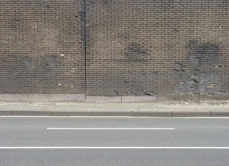 road,sidewalk and brown beige tiled worn wall