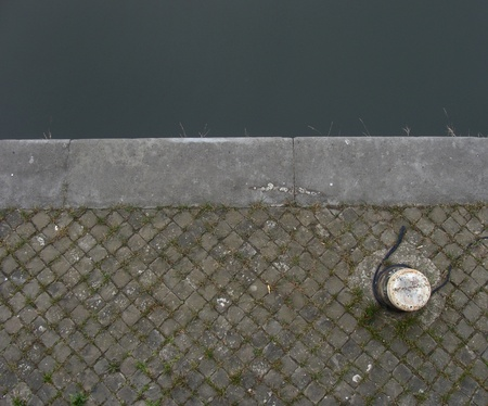 sidewalk at harbour with mooring-post to attach boat                                photo