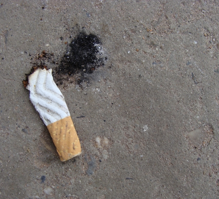 cigarette butt with ash showing shoe print Stock Photo