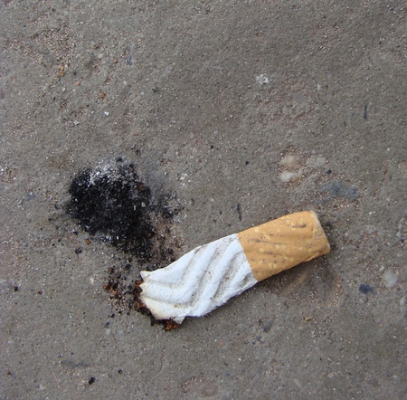 cigarette butt with ash showing shoe print photo