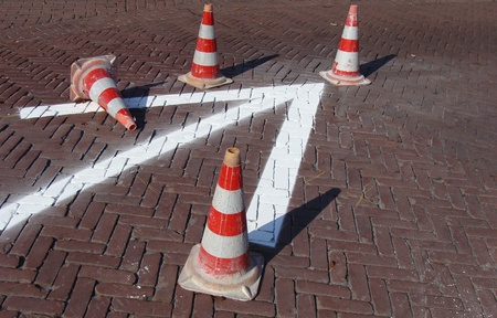 arrow with typical orange and white traffic cone on pavement photo