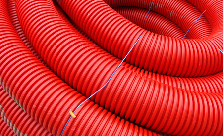 plastic conduit: red rolled up wire pipe on an industrial construction site