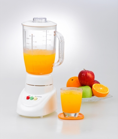 Fruits and orange juice blender machine on clean background  photo