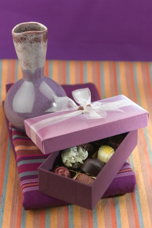 Beautiful chocolates box display on colorful fabric background and vase  photo