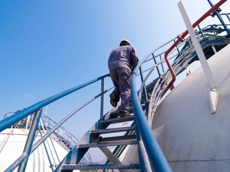 industria quimica: El ingeniero de caminar a lo largo de la escalera del tanque de gas para el control de las válvulas de gas