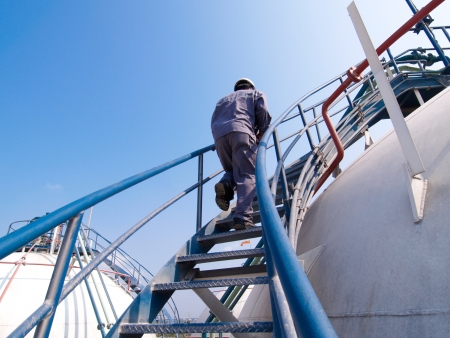 gas plant: The engineer walking along the ladder of the gas tank for checking the gas valves  Stock Photo