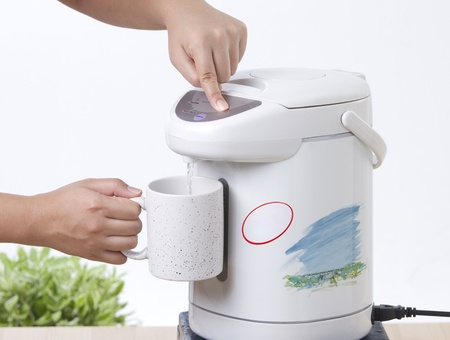 Pouring hot drinking from electric water boiler pot Stock Photo - 16984653