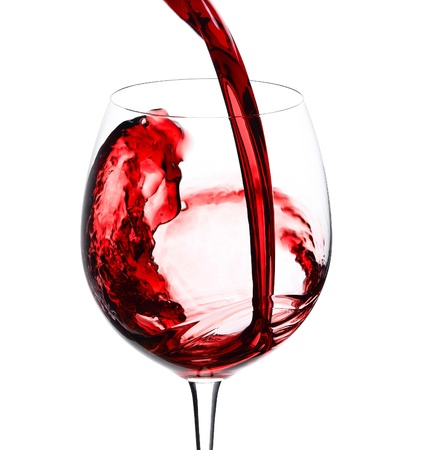 Pouring red wine to wine glass isolated on white photo