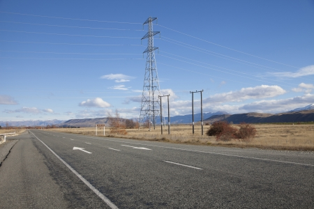 electricity grid: Beautiful road and high voltage electric pole across the land against the blue sky and clouds in New Zealand Stock Photo