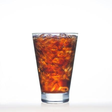 번쩍이는 콜라 음료는 흰색에 고립 된 유리에 소다와 얼음 엉