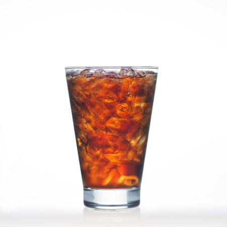Espumosos bebidas de cola pizca de soda y hielo en el vaso aislado en blanco
