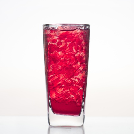 Sweet and cold pomegranate fruit juice in glass isolated on white background