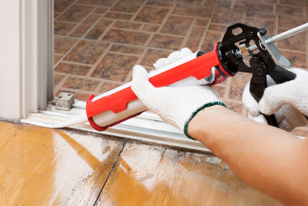 Worker applies silicone caulk on the wooden floor for sealant waterproof Reklamní fotografie - 25623775