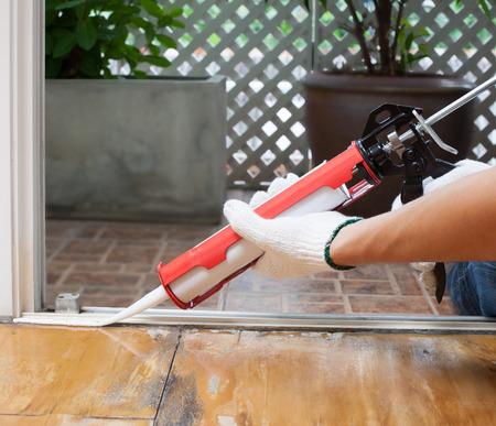 Карпентер применяется силиконовый конопатить на деревянном полу для герметика водонепроницаемый Фото со стока